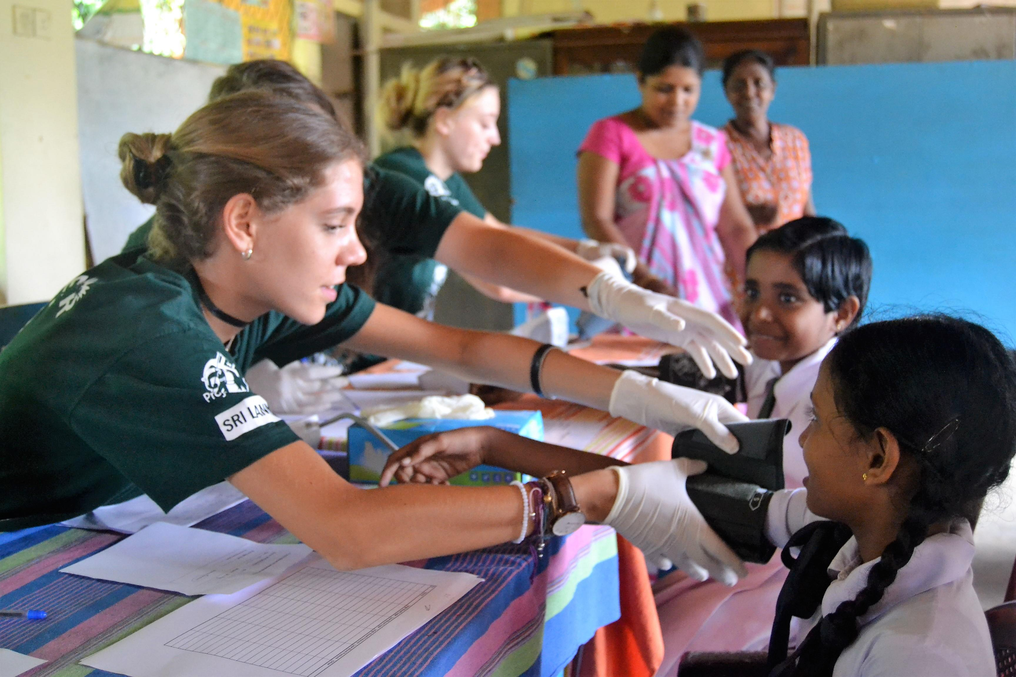 A female intern takes the blood pressure of local children during her medical internship in Sri Lanka with Projects Abroad.